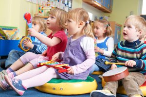 Group Of Children in early learning center Taking Part In Music Lesson