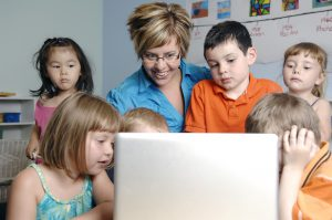 ELC trends with technology teacher using laptop with children